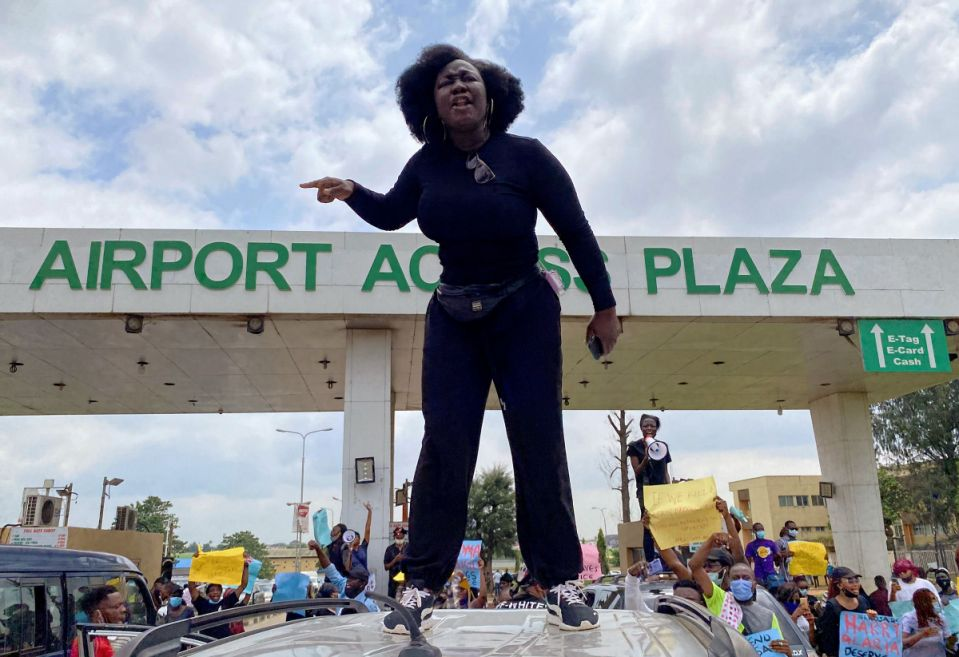 A demonstrator stands atop a vehicle and shouts slogans as others carry banners while blocking a road leading to the airport, during a protest over alleged police brutality, in Lagos Nigeria, 2020